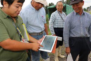 JA職員が生産者に、水田の日射量や水量などのデータをタブレット端末で説明