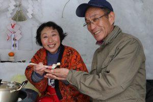 地元の祭りで、観光客をかまくらのなかでもてなすJA秋田ふるさとの女性部員